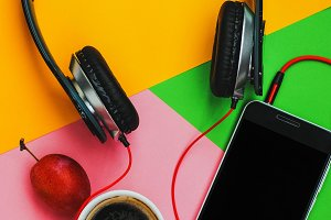 Top view accessories office desk.smartphones headphones on colorful background with copy space.