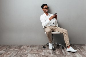 Man sitting in a chair and holding mobile phone