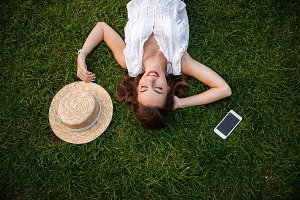 Woman lies on grass outdoors. Eyes closed.