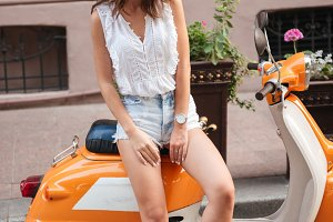 Cheerful young woman near scooter outdoors