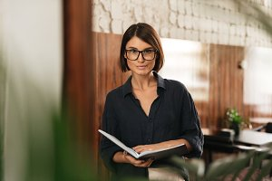 Smiling Female manager in eyeglasses with documents in hands