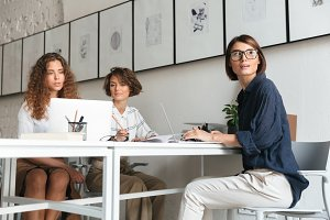 Three pretty women working by the table