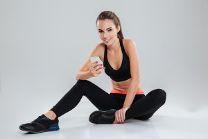 Smiling fitness woman sitting on the floor with smartphone