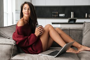 Young pretty asian woman in sweater holding cup of coffee