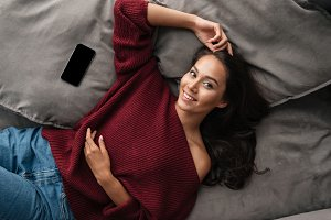 Smiling asian woman in sweater lying on a couch