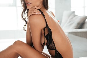 Side view of a young seductive woman in sexy lingerie