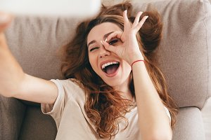 Happy emotional woman making funny selfie