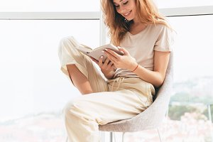 Young pretty woman reading book near window