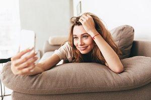 Happy emotional pretty lady make selfie by phone.