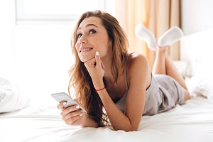 Happy emotional pretty lady lies on bed chatting by phone.
