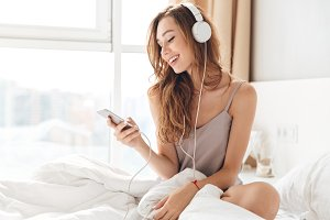Smiling lady in pajamas listening music with smartphone and headphones