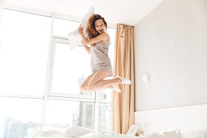 Happy pretty lady jumping on bed holding pillow