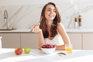 Smiling happy woman eating fresh berries from a bowl