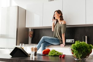 Happy casual woman sitting on the table in kitchen