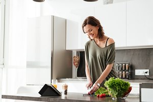 Smiling casual woman cuts vegetable by the table on kitchen