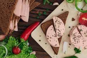 sandwich of rye bread with boiled sausage on a rustic wooden background