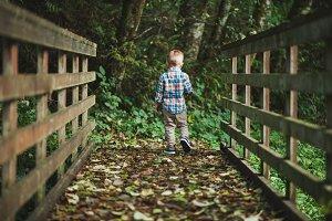 Little Boy Walking Across Bridge