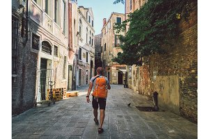 Tourist goes a view with his back to Venice, Italy with an orange backpack and camera on his neck along the old streets