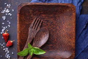 Empty wooden plate, cutlery, salt, pepper and basil