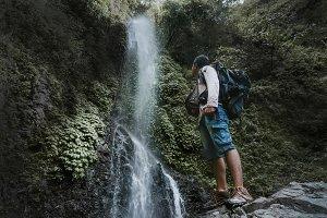 Male tourist enjoying near waterfall