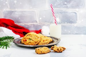 Milk and cookies for Santa Claus and Santa's hat over wooden bac