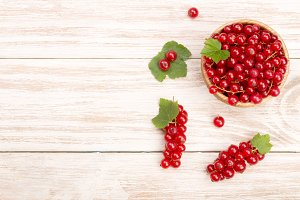 Red currant berries in a wooden bowl with leaf on the light wooden background with copy space for your text. Top view