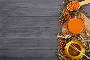 Sea buckthorn juice or tea with honey on a black wooden background with copy space for your text. Top view