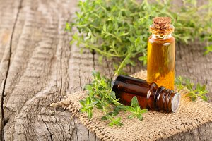 Bottle of essential oil with herbs thyme on an old wooden background