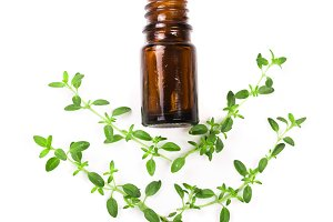 Bottle of essential oil with herbs thyme isolated on white background