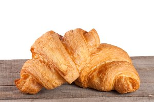 two croissant on a wooden table with white background