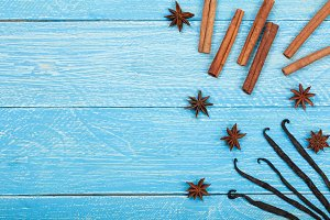 vanilla sticks, cinnamon, coffee beans and star anise on blue wooden background with copy space for your text. Top view
