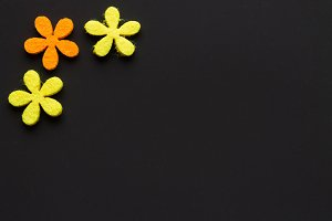 of felt flowers on dark background.