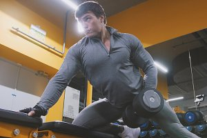 Young muscular man athlete lifting dumbbells