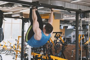 Young man athlete doing pull-up bar abdominal exercise in gym