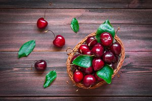 Cherries with leaves in a basket on wooden background