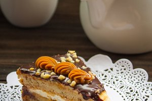 Piece of cake, teapot and lilac on a wooden background