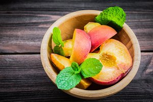 Peaches in plate on a wooden background