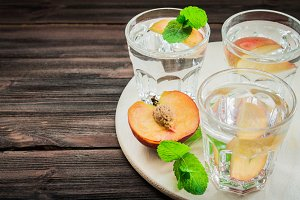 Water with peaches on a wooden background