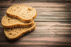 Slices of rye bread on a wooden background