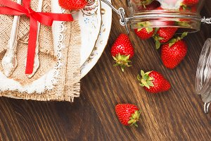 Tableware and silverware with red ripe strawberries