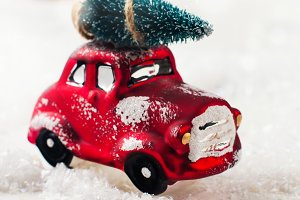 Miniature red car carrying fir tree on Christmas background