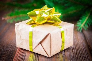gift with golden bow under the Christmas tree branches