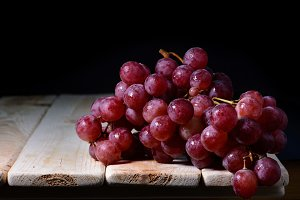 bunch of red grapes on wooden table