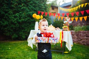 surprise for the birthday. the boy is holding a box with a gift in the yard on the background of a festive table with a cake. dressed in a black suit