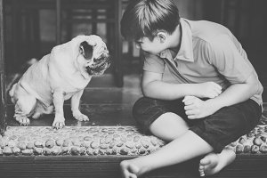 Caucasian boy with a pet pug