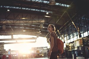 woman in the hall of the airport terminal with small backpack