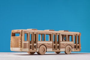 Toy, wooden bus on blue.