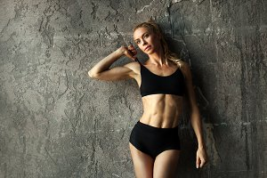 Fit female fitness model posing and showing her muscular body with strong and tanned abdominal muscles in front of concrete wall