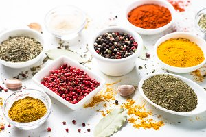 Various spices in a bowls on white table.