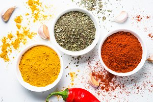 Various spices in a bowls on white background.